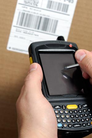 휴대용 바코드 스캐너를 사용하는 남성 손 그림 UPC 상자 레이블이있는 인벤토리를 가져 오는 Enterprise Digital Assistant 컴퓨터.