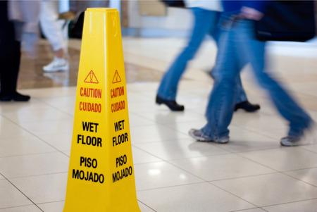 Attention Wet Floor signe avec des gens qui marchent en arrière-plan