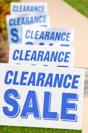 Clearance sale signs in a row outside along a store sidewalk. 版權商用圖片