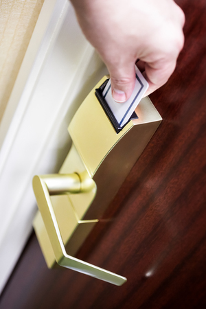 Persons hand unlocking a hotel room door by inserting a key card into an electronic door lock.