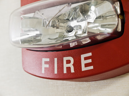 Red fire alarm with strobe light mounted on a wall as part of a fire protection system. Stock Photo