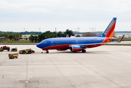 A Southwest Airlines airplane being towed to a gate by a ground crew tow tractor at Orlando International Airport in Florida USA
