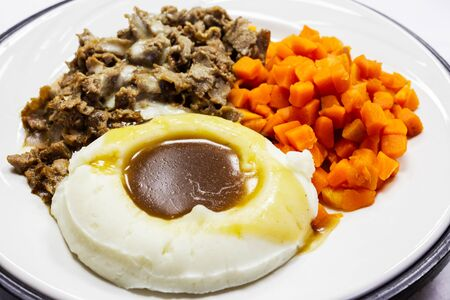 Plate of hospital food with beef, chopped carrots, mashed potatoes, and gravy.