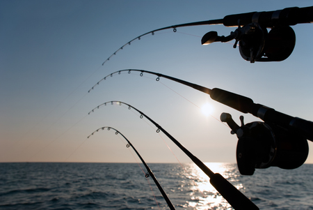 Fishing poles at sunrise. Picture of four fishing poles off the side of a boat during sunrise.