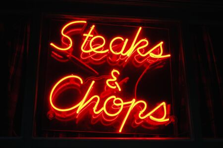 Steaks and chops neon sign in a restaurant window