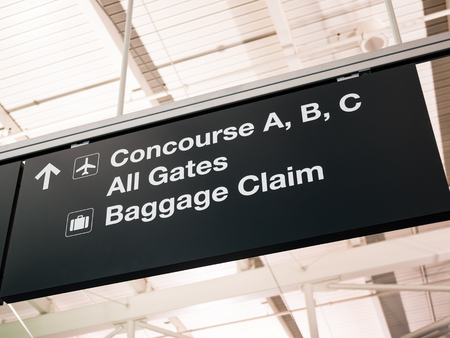 Airport concourse, gates, and baggage claim sign