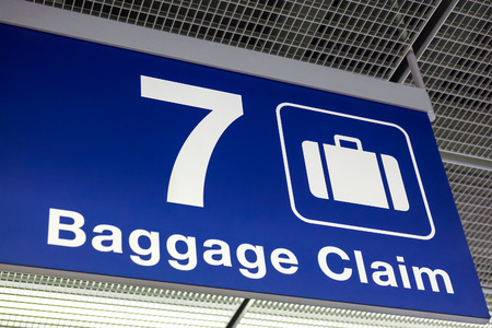 A blue airport baggage claim sign hanging from the ceiling Reklamní fotografie