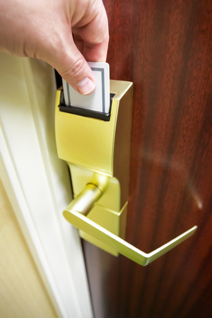 Persons hand inserting a keycard into a hotel room electronic door lock to unlock the door Stock Photo