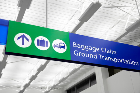 buss: Airport baggage claim and ground transportation sign with suitcase, bus, and taxi symbols. Sign is blue and green and hangs from the ceiing. Image Copyright © 2009 Paul Velgos with All Rights Reserved.