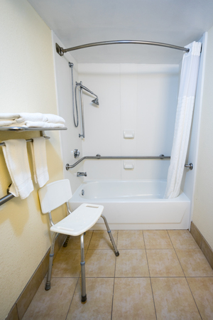#77826858   Hotel Handicap Bathroom With A Chair And Shower Bathtub  Handrails