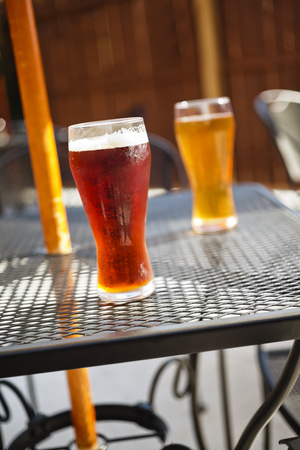 Two beer glasses with dark and light beer on an outside mesh patio table
