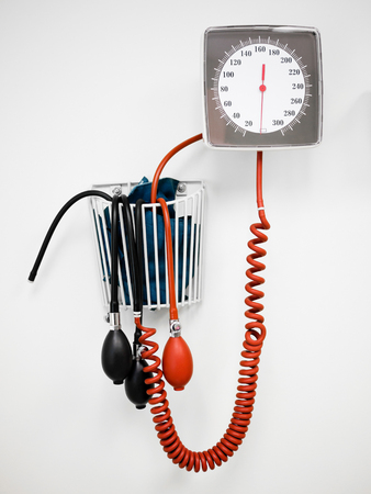 Sphygmomanometer Blood Pressure Gauge -Traditional bulb and dial sphygmomanometer blood pressure gauge hanging on a wall in a medical clinic doctors office Reklamní fotografie