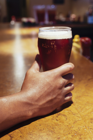 African American persons hand holding a beer glass at a bar