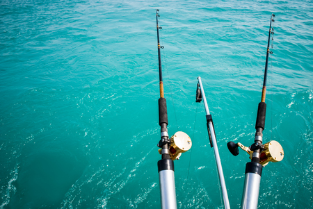 Picture of two commercial fishing poles over turquoise water with copy space Фото со стока