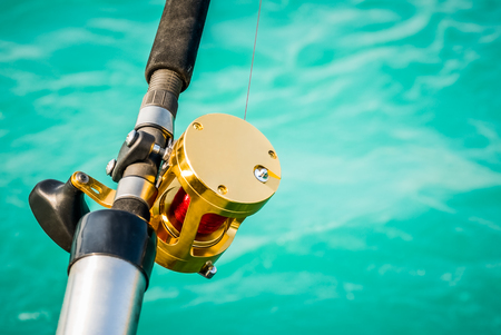Picture of a fishing pole and reel over turquoise colored water with copyspace for adding text Stock Photo