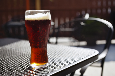 Beer glass with dark beer on an outdoor mesh patio table