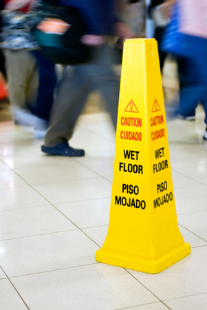 Photo of a Caution Wet Floor yellow cone sign with people walking in the background.  Concept is legal liability for lawfirms, lawyers, and attorneys for personal injury or slip and fall accidents. Stock Photo