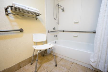 Handicap Hotel Bathroom with Shower Bathtub Hand Rails and a Chair Foto de archivo