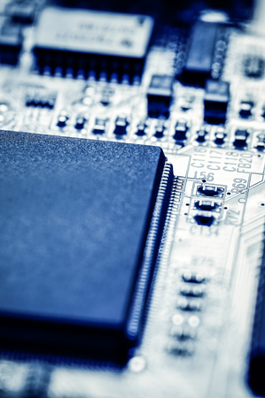 Picture of a computer circuit board chips macro blue tinted.