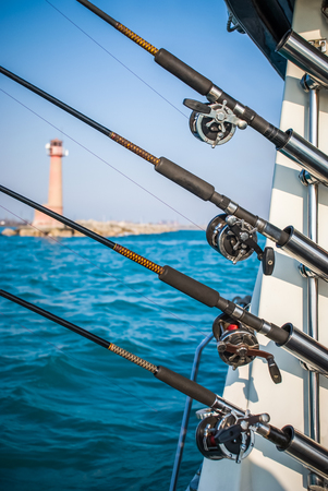 Four fishing poles mounted to a charter boat with turquoise water and a lighthouse in the background.