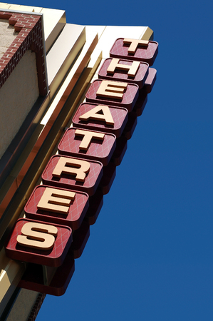 Movie theatres sign picture with a blue sky