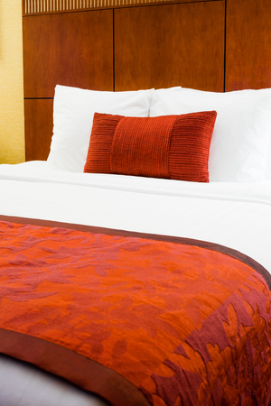 Hotel room bed with burgandy colored pillow and duvet.