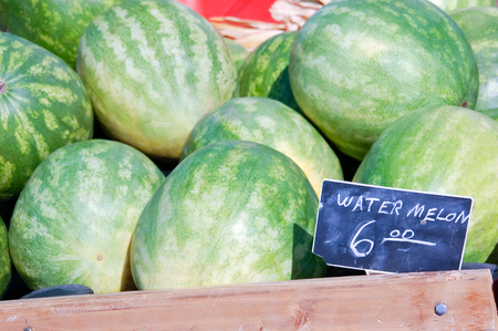 Picture of watermelons at a farmers market with a price sign