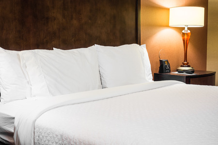 Modern Hotel Room Bed With A Lamp On A Nightstand Stock Photo