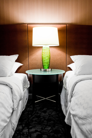 Modern hotel room with a lamp in between two beds
