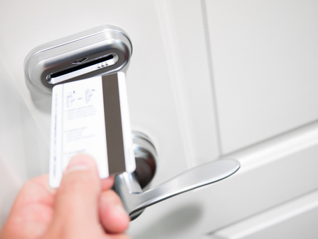 A persons hand inserting a keycard into an electronic door lock security system on a hotel room.