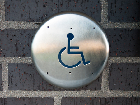 Handicapped automatic door opener button switch on a brick wall