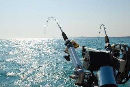 ボートに乗って釣りロッド。ボートの後ろにポール ホルダーに 2 つの釣り竿の画像。