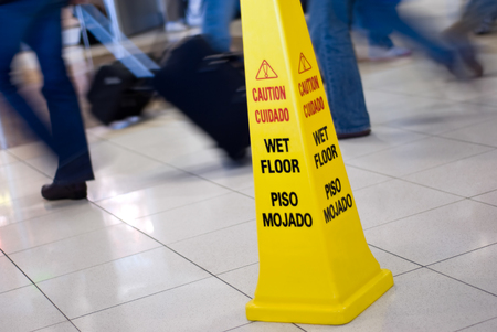 Picture of a Caution Wet Floor yellow cone sign with blurred motion people walking in the background