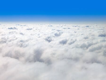 Picture of clouds from above with a blue sky horizon and copy space.