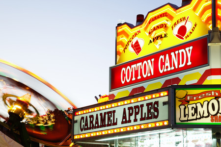 Carnival Concession Stand Sign - Photo of amusement park ride and concession stand food sign with cotton candy and caramel apples. Stockfoto