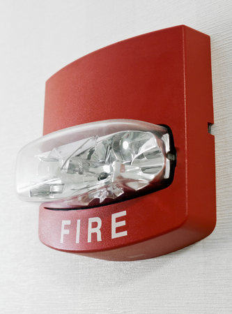 lighted: Red fire alarm with strobe light mounted on a wall as part of a fire protection system. Stock Photo