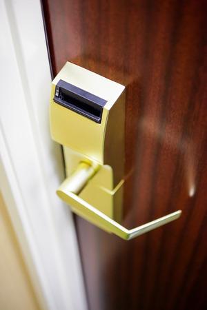 Hotel room brass electronic door lock and handle on a wood door Stock Photo - 77879019