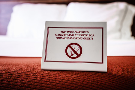 Picture of a No Smoking Sign on a hotel room bed. The sign reads This room has been serviced and reserved for our non-smoking guests. Stock Photo