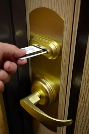 カードキーでホテルの部屋のドアのロックのロック解除人の手の画像