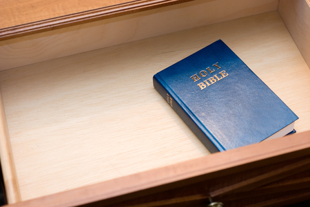 Picture of Holy Bible in a hotel room nightstand open drawer with copy space for adding text Stock Photo