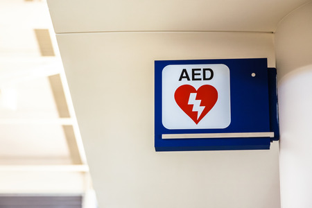 Automated External Defibrillator AED sign mounted to a wall at an airport. Stock Photo
