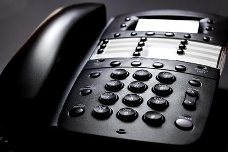ビジネス電話。黒地にモダンな黒の固定電話。
