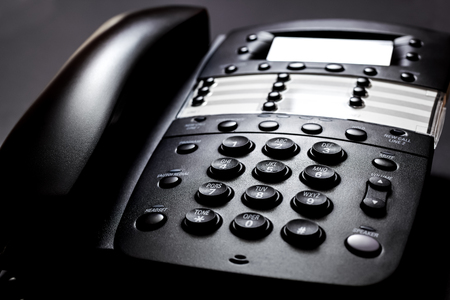 Business Telephone. Modern black landline telephone on a black background. Stock Photo