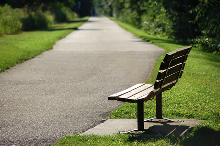 公園沿いの散歩道やサイクリング道のベンチの画像。