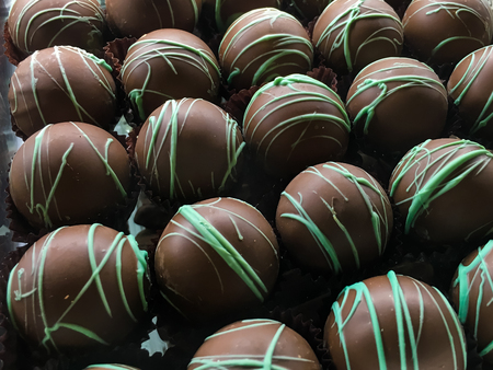 Round chocolate candies with green topping in rows