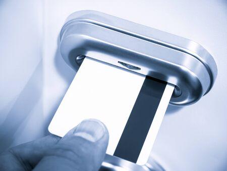ホテルの部屋の電子キーカードのドアロックに磁気キーカードを挿入する人の手