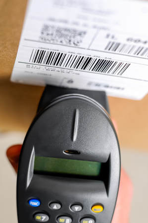 Barcode scanner reader with box UPC label being held by a peron's hand Reklamní fotografie - 77879057