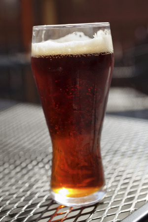 屋外メッシュ パティオ テーブルの黒ビールとビアグラス