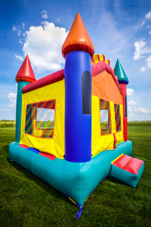 Bounce house inflatable jumpy castle in a large open yard. Image Copyright � 2009 Paul Velgos with All Rights Reserved. Stock Photo - 77879063