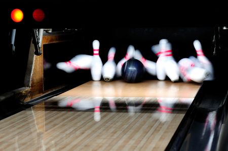 Picture of  bowling ball hitting pins scoring a strike Stock Photo